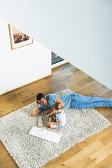 Father with daughter on rug playing glockenspiel