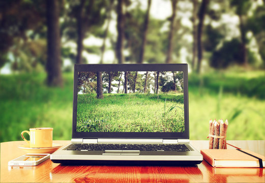 laptop over wooden table outdoors and blurred background of trees in the forest