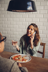 Young couple eating pizza in restaurant, woman talking on the phone