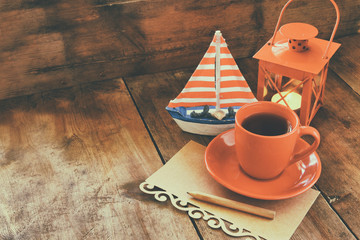 red cup of tea and letter paper next to vintage decorative boat and lantern on wooden old table. retro filtered image