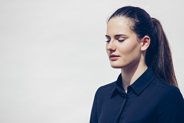 Portrait of young woman with ponytail and closed eyes in front of white background