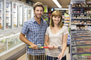Portrait of cheerful young couple in supermarket. Looking camera