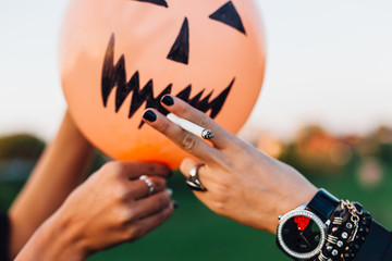 Girl having fun with Halloween balloon with a cigarette