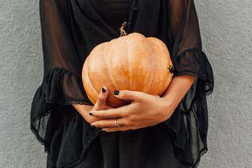 Girl in black holding a pumpkin