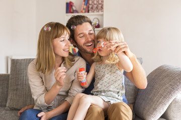 Cheerful parents and daughter blowing bubbles in  modern house