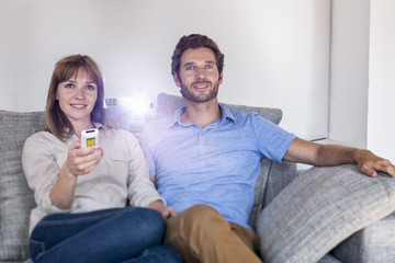 Couple watching a movie with a video projector, on sofa