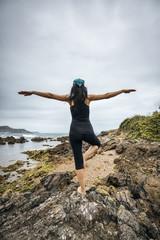 Spain, Asturias, Gijon, woman doing yoga on a rocky beach