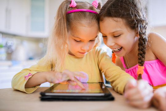 Two little sisters play on a Tablet PC