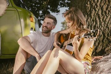 Couple making music at tree beside van