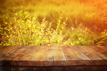 vintage wooden board table in front of dreamy and abstract landscape with lens flare.