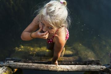 Girl getting into a lake