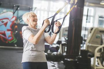 Happy senior woman in gym doing suspension training