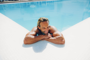 Portrait of smiling man in swimming pool leaning on pool edge