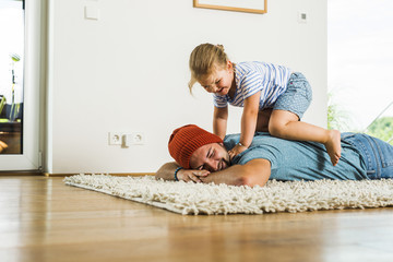 Daughter kneeling on father's back lying on floor