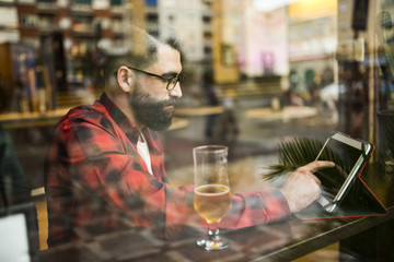 Adult bearded hipster style man touching tablet in bar and drinking alchohol near to window