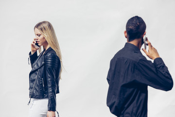 Two young people telephoning with smartphones