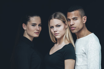 Group picture of two young woman and young man in front of black background