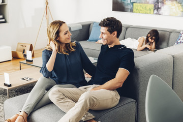 Smiling couple in living room with daughter using digital tablet in background