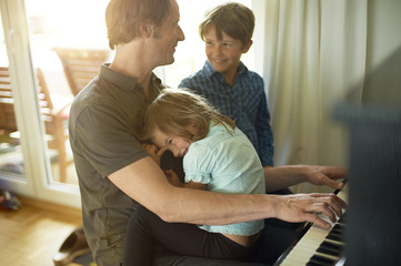 Father playing piano with daughter on his lap, son watching