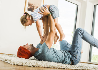 Father lying in rug lifting up happy daughter