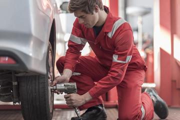 Car mechanic at work in repair garage, changing tires, impact driver