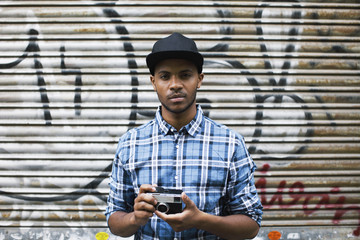 Portrait of young man with baseball cap and camera in front of roller shutter