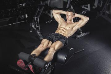 Physical athlete exercising with glute ham developer