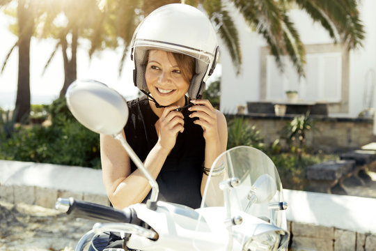 Spain, Majorca, Alcudia, portrait of smiling young woman with motor scooter