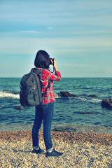 hipster girl photographing sea
