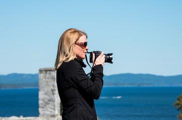 Blond woman thaking photographs