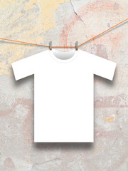 T-shirt hung with clothespin on concrete wall background
