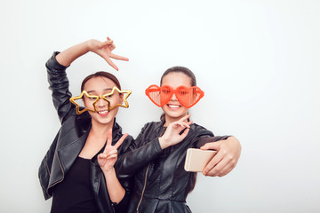 Asian girls in the funny sunglasses. They pose, grimace and look at the camera. Hair removed. The skin is clean. Making selfie.