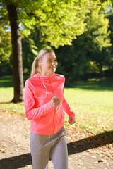 junge blonde frau joggt duch den park