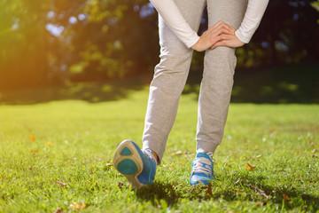 frau dehnt die wade beim joggen