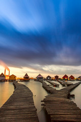 Sunset lake Bokod with pier and fishing wooden cottages
