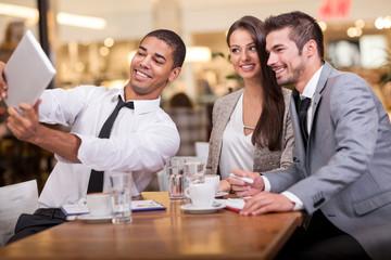 business people taking selfie in restaurant