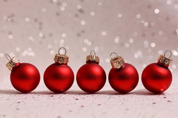 Vijf rode kerstballen met glitters op de achtergrond