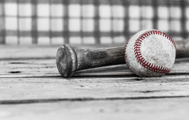 horizontal image of black and white with selective color of a baseball and bat on a wood surface with a checkered background with room for text.