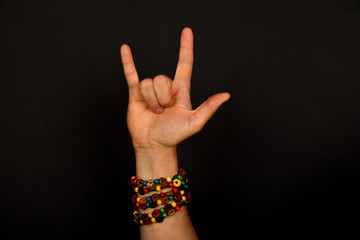 Hand with devil horns and colorful beads isolated on black