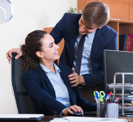 Top manager flirting with subordinate official at workplace