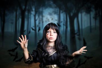 kleines Mädchen als Hexe verkleidet, im Wald mit vielen Fledermäusen