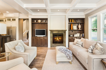 Beautiful living room interior with hardwood floors, coffered ceiling, and roaring fire in fireplace in new luxury home