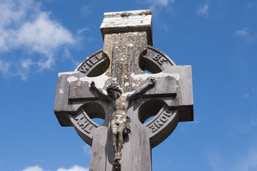 Crucifix on a Celtic Cross Gravestone, with blue sky above.