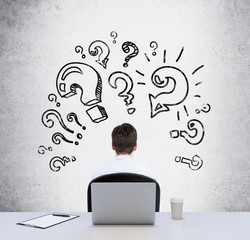 Rear view of a sitting person at the working desk who is looking for the best solution of the problem. Question marks are drawn on the concrete wall.