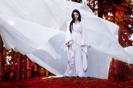 Hero of Eastern philosophy. Asian woman in white kimono holding