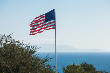 American flag waving in the breeze with a background of blue