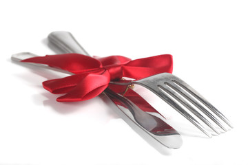 Fork and knife with christmas ribbon, isolated on white, shallow