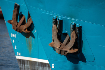 Rusted rugged Anchor on blue fishing ship