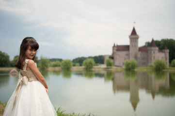 girl in dress smiling in front of the lake and the castle