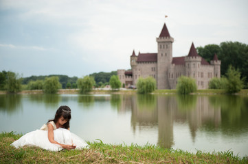 girl in ball gown picking flowers in front of the lake and the castle